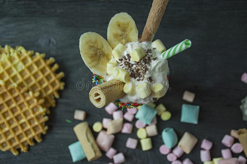 Banana milkshake with ice cream and whipped cream, marshmallows, cookies, waffles, served in a glass cup decorated with royalty free stock photo