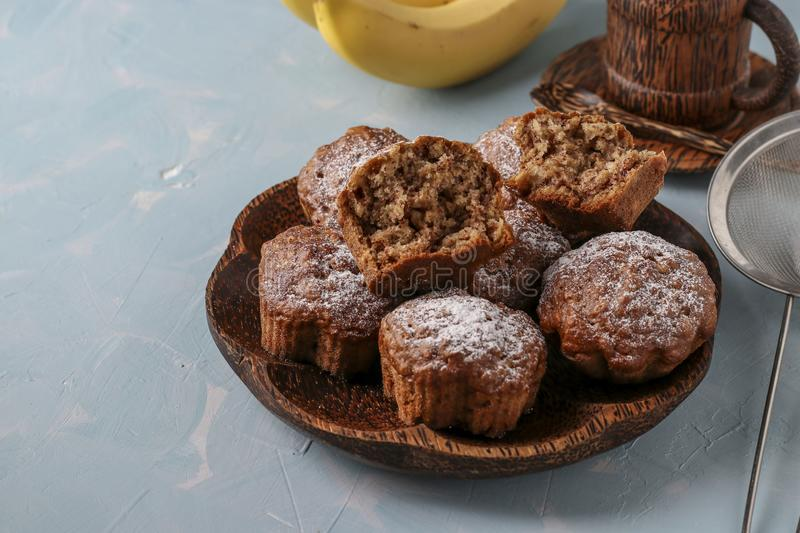 Banana muffins with oatmeal flakes sprinkled with icing sugar on a coconut plate, horizontal orientation. Copy space stock photos
