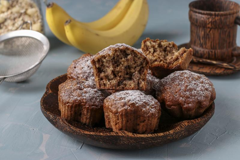 Banana muffins with oatmeal flakes sprinkled with icing sugar on a coconut plate, horizontal orientation. Closeup royalty free stock photos