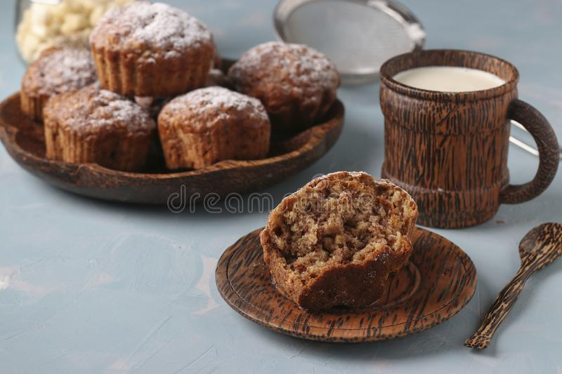 Banana muffins with oatmeal flakes sprinkled with icing sugar on a coconut plate, horizontal orientation. Banana muffins with oatmeal flakes sprinkled with icing royalty free stock images