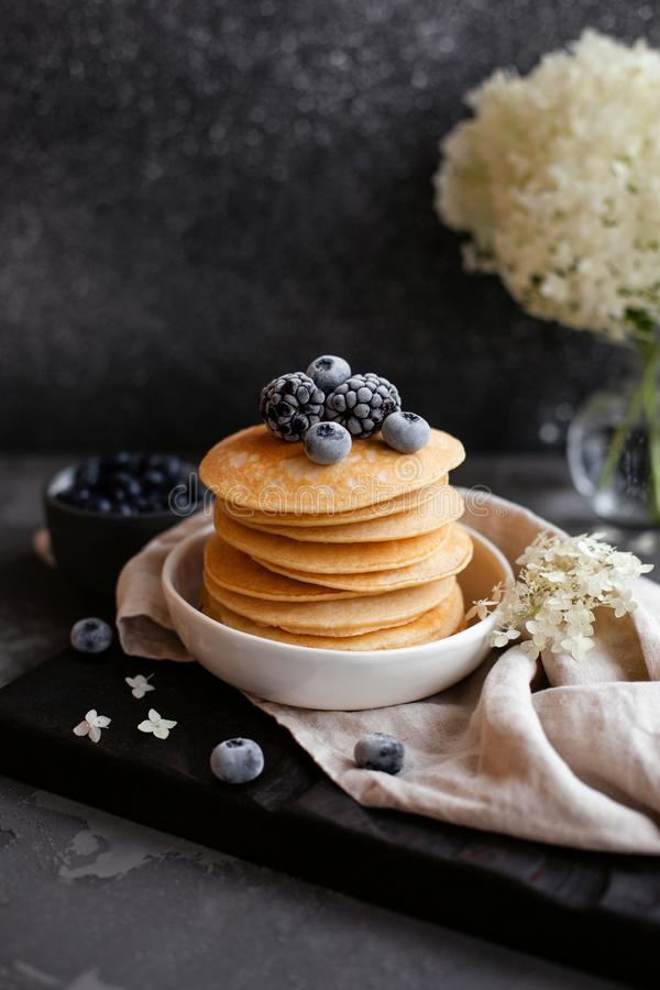 Banana oat pancakes with frozen blueberries. Morning light royalty free stock image