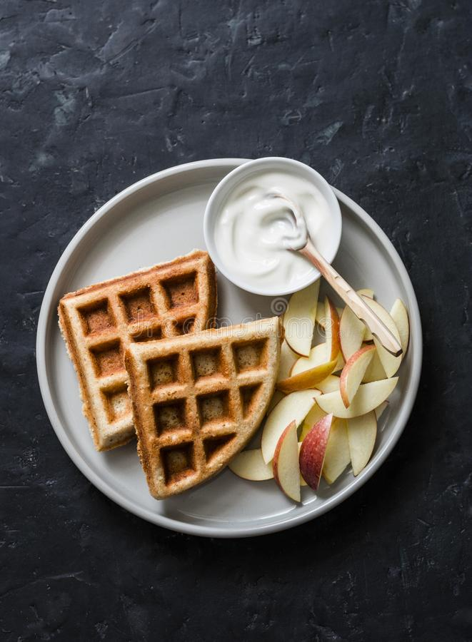 Banana oatmeal waffles with apple and yogurt on a dark background, top view. Delicious breakfast, dessert royalty free stock images