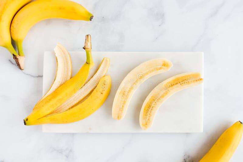 Banana Peel and Bananas on White Marble Board. Bananas, banana peel and a peeled banana cut lengthwise in half on white marble board and marble background. Top royalty free stock photo