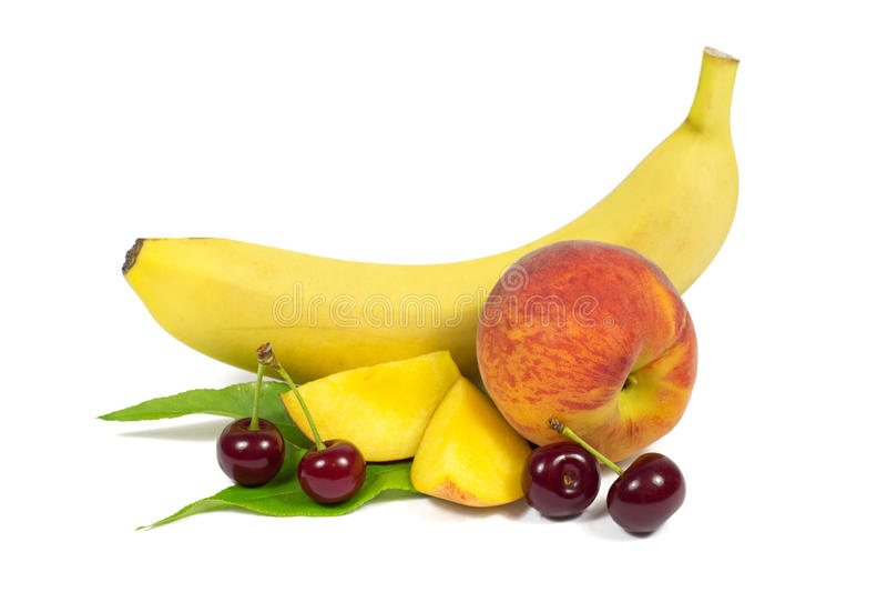 Banana, pesche e ciliege sulla foglia verde isolata su bianco fotografia stock libera da diritti