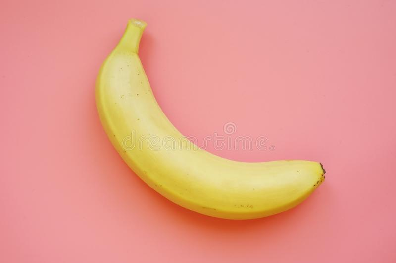 Banana on a pink background. Colorful fruit pattern. Concept stock image