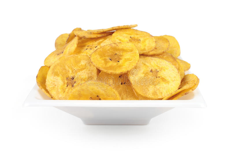 Banana. Several banana chips isolated on a white plate stock photo
