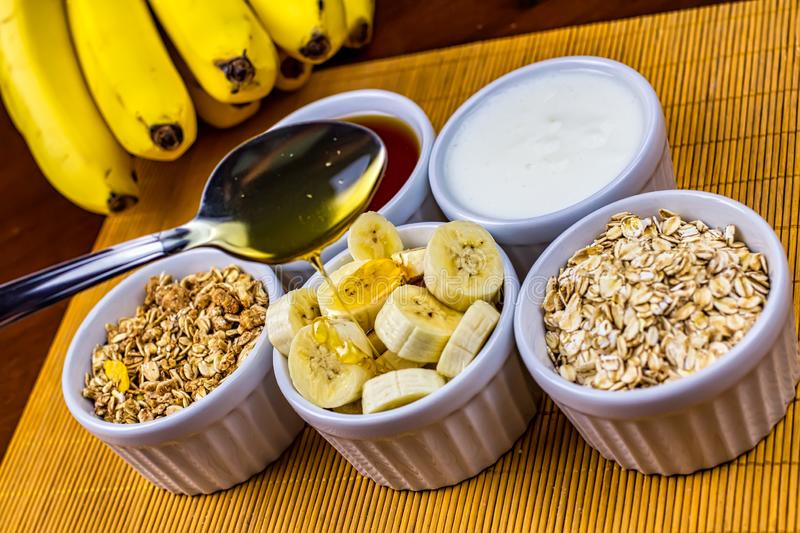 Banana sliced on ramekin and spoon pouring honey with oatmeal, granola, plain yogurt and honey as side dishes under bamboo mat royalty free stock photography