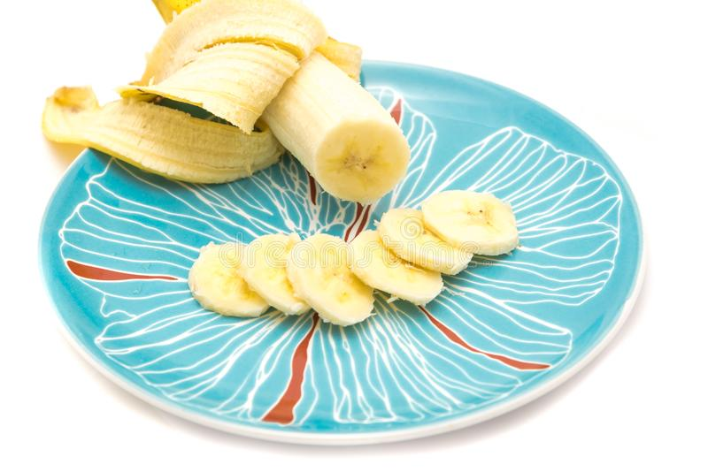 Banana slices on serving plate isolated. Sliced Banana on a serving plate isolated on white. Food background with clipping path and copy space royalty free stock photos
