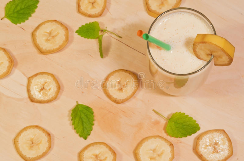 Banana smoothie on wooden background royalty free stock images
