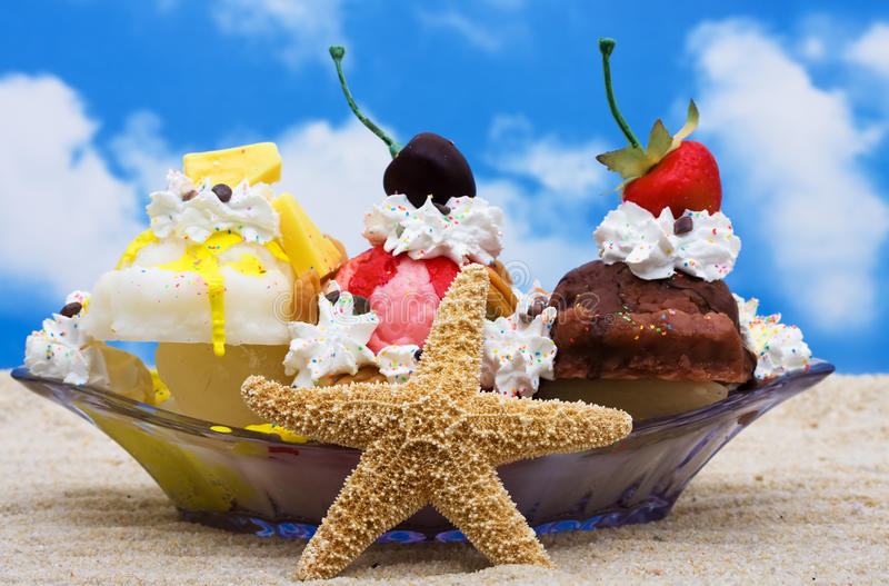 Banana Split. A banana split ice cream sitting on sand with a sky background stock image