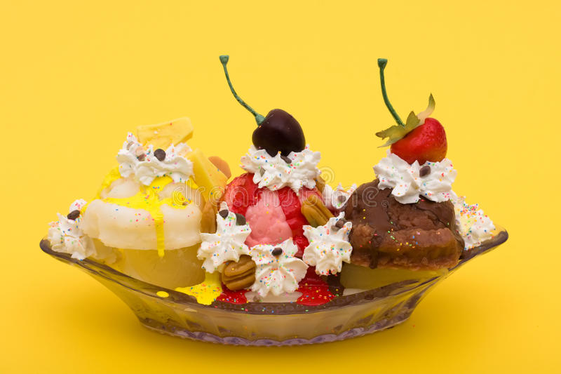 Banana Split. A banana split ice cream on a yellow background, ice cream sundae royalty free stock photography