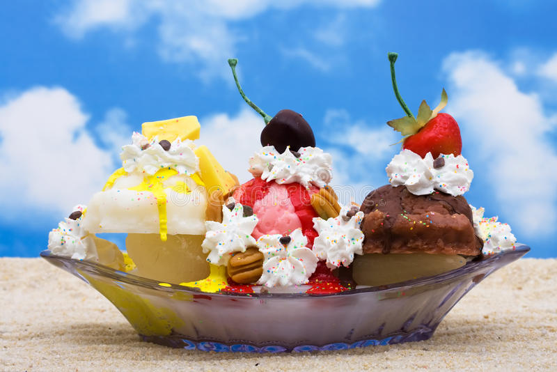 Banana Split. A banana split ice cream sitting on sand with a sky background royalty free stock photo
