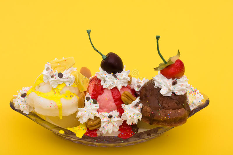 Banana Split. A banana split ice cream on a yellow background, ice cream sundae stock image