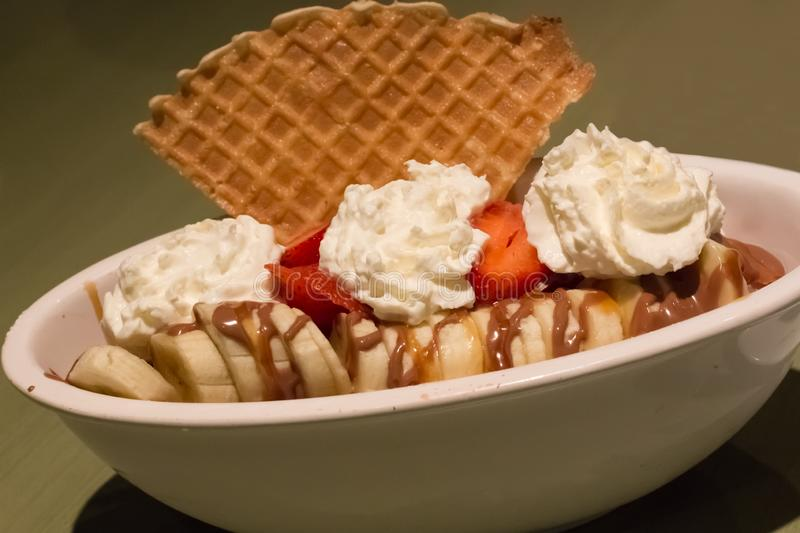 Banana Split with Ice Cream. Banana Split with Vanilla Ice Cream, Strawberry, chocolate sauce and waffle piece in a long bowl stock image