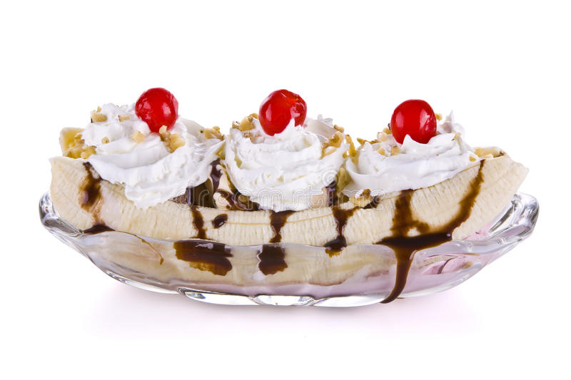 Banana split. A banana split with whip cream and cherries in a glass bowl isolated on a white background stock image