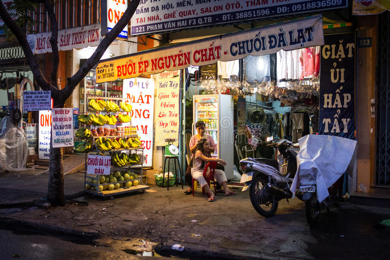 Banana Store And Laundry Service In Vietnam. View of a store inn district Tan Binh, Ho Chi Minh city, Vietnam at night time. The store sells fruit juices stock image