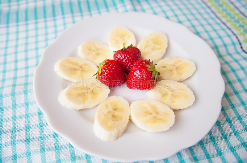 Banana and strawberries on white plate and a colorful napkin stock photos