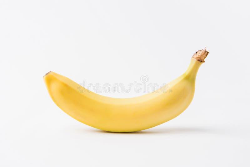banana unpeeled crua que coloca no branco fotografia de stock