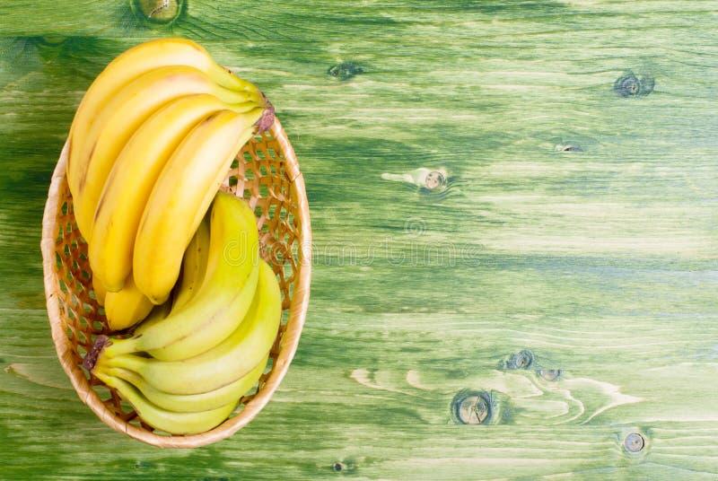 Banana verde e amarela em uma cesta de vime em um quadro verde fotos de stock royalty free