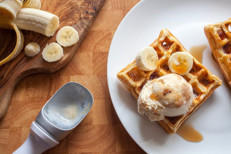 Banana waffles dessert with ice cream and maple syrup close-up royalty free stock image