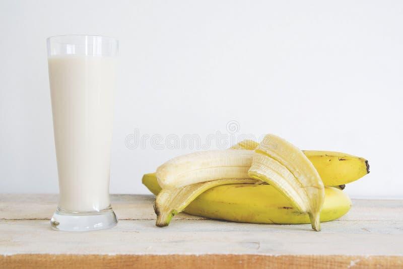 Bananas amarelas naturais em uma tabela de madeira branca e em um batido da agitação de fruto contra um fundo branco espaço vazio fotografia de stock royalty free