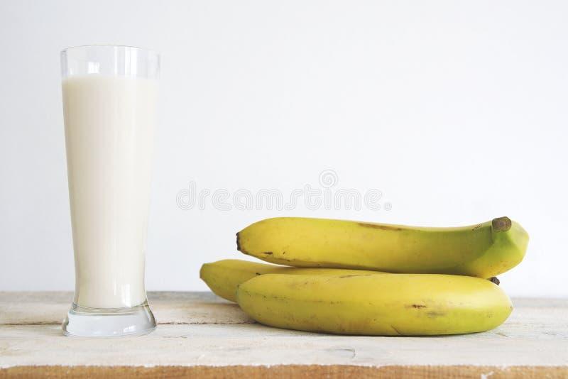Bananas amarelas naturais em uma tabela de madeira branca e em um batido da agitação de fruto contra um fundo branco espaço vazio fotos de stock