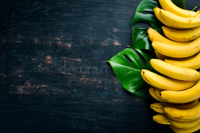 Bananas on a black wooden surface. Tropical Fruits. Top view. Free copy space stock image