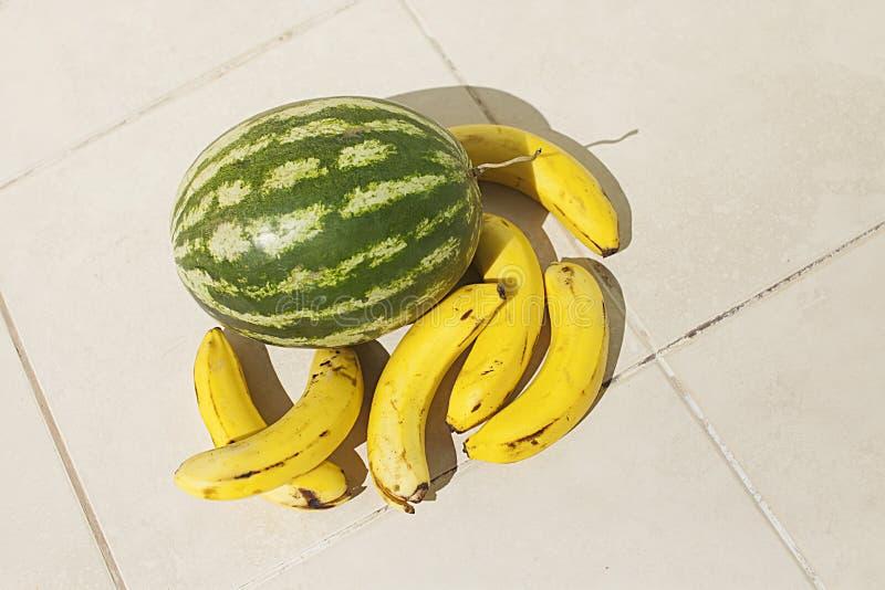Bananas e melancia amarelas no assoalho fotografia de stock