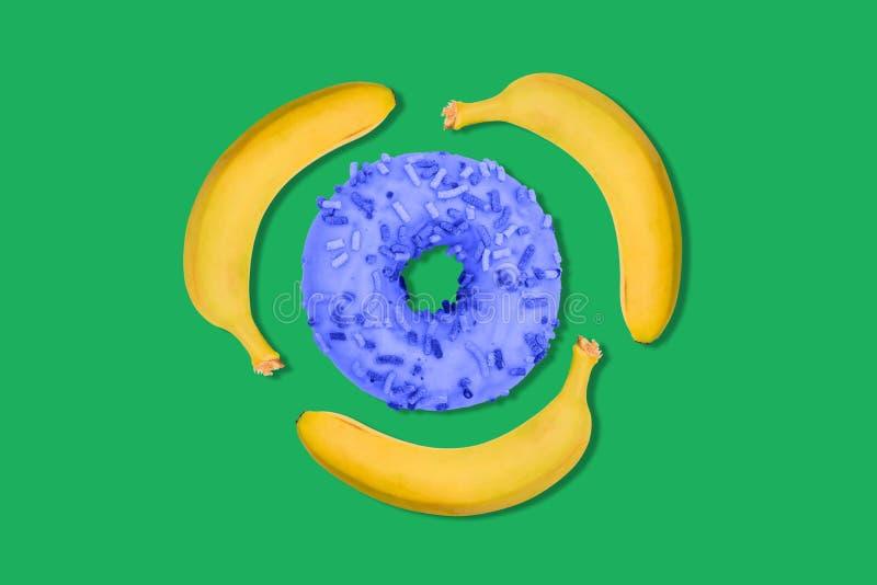 Bananas e uma filhós azul em um fundo verde O fruto e o fast food estão girando em um círculo Alimento útil e não saudável imagens de stock royalty free
