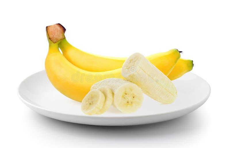 Bananas em uma placa no fundo branco fotos de stock royalty free