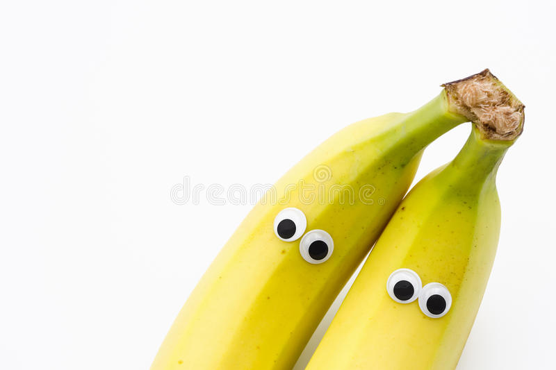 Bananas with googly eyes on white background. Banana face royalty free stock photography