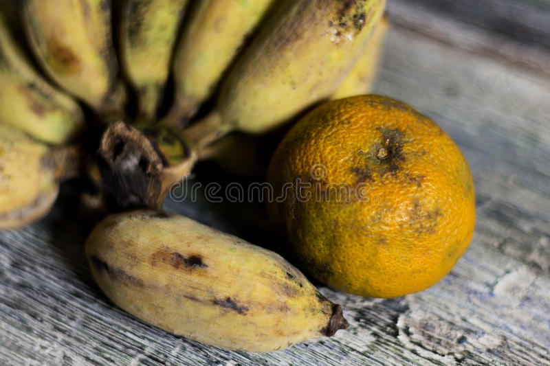 Bananas and oranges to wither on wood table stock photos