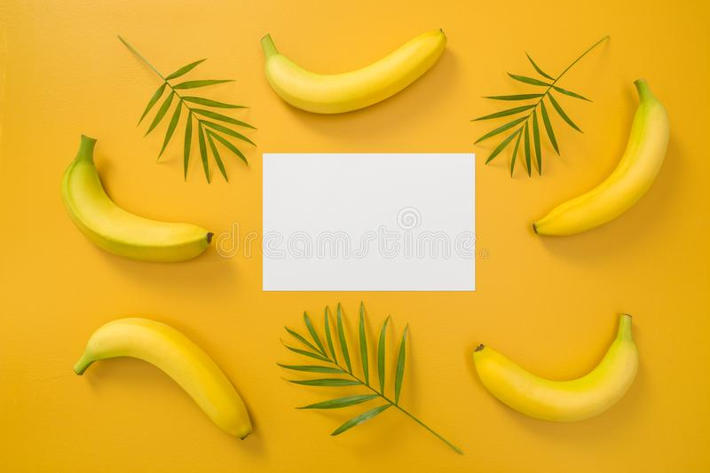 Bananas, palm leaves and blank paper sheet royalty free stock photography