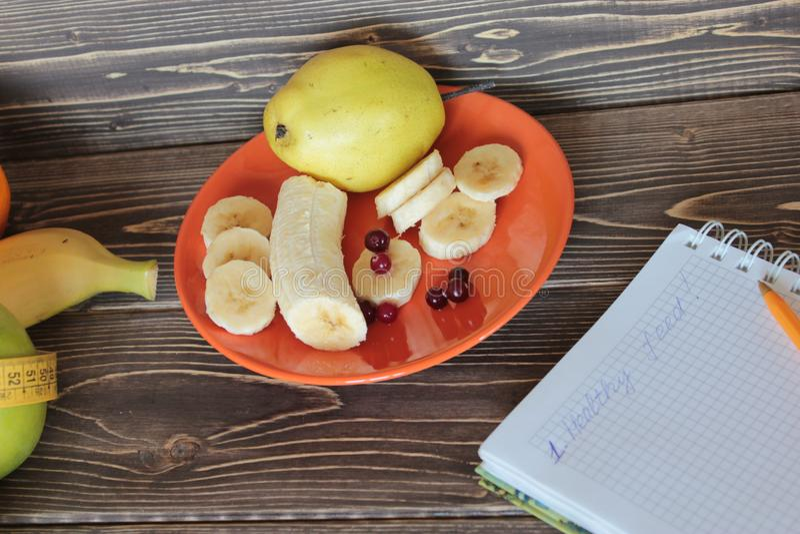 Bananas, peras, bagas e caderno em uma tabela imagem de stock royalty free