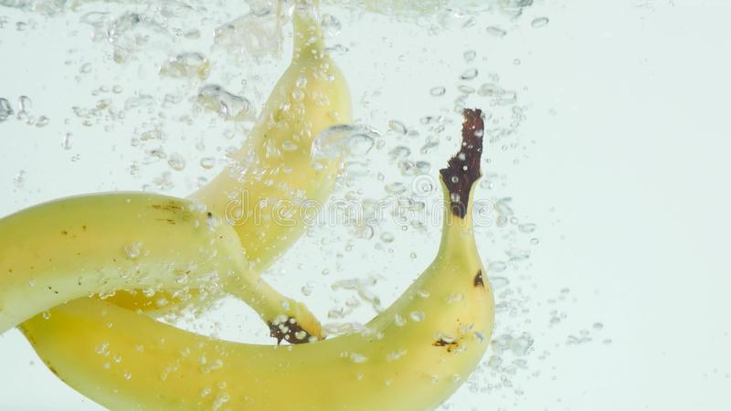 Bananas plunging into water on white background in slow motion stock photography