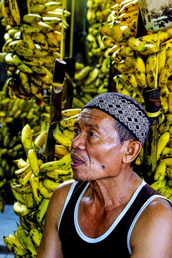 A bananas seller at traditional market. A banana merchant is attending his stall waiting for costumers to come, wearing modest costume and a cap royalty free stock photos