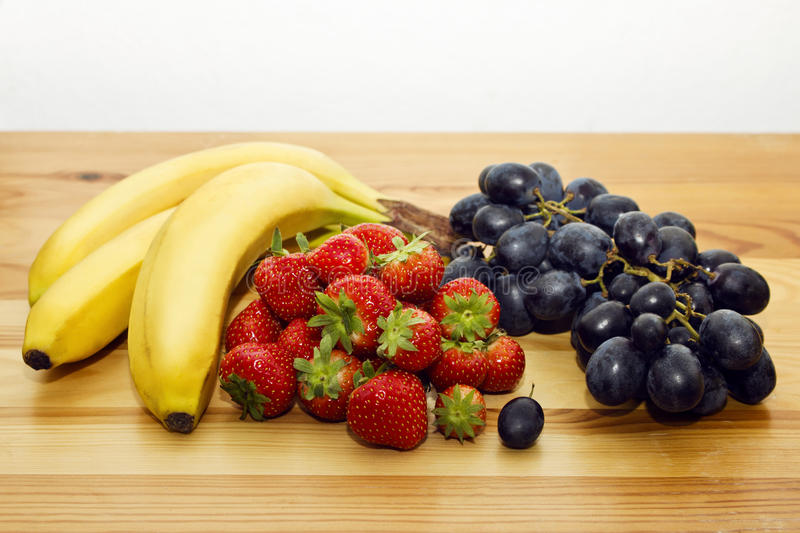 Bananas, strawberries and blue grapes on the table. royalty free stock images