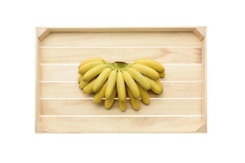 Bananas on wooden tray. Top view of fresh ripe bananas on wooden tray isolated on white stock image