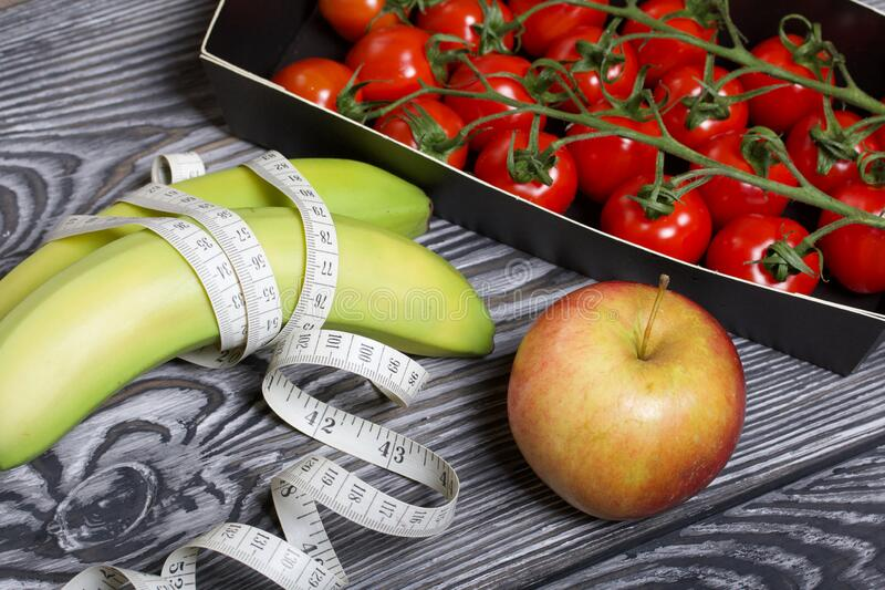 Bananas wrapped in measuring tape, apple bunch of tomatoes. On brushed pine boards. Symbol of World No Diet Day.  stock photos