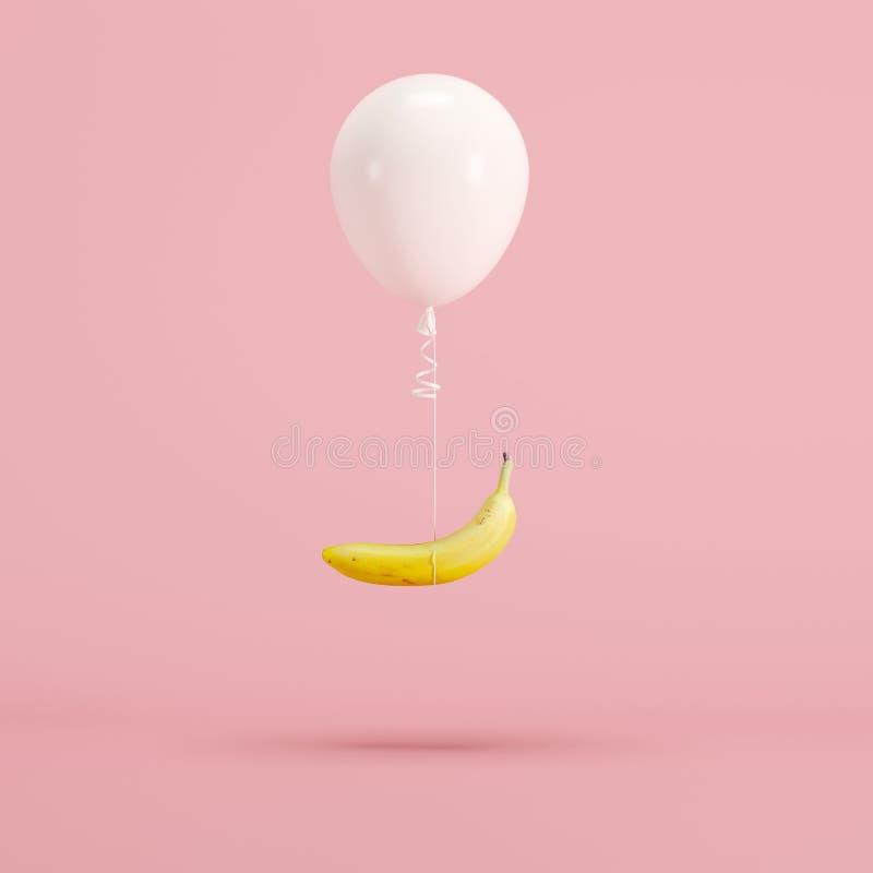Banane attachée avec le ballon blanc sur le fond rose en pastel photos stock