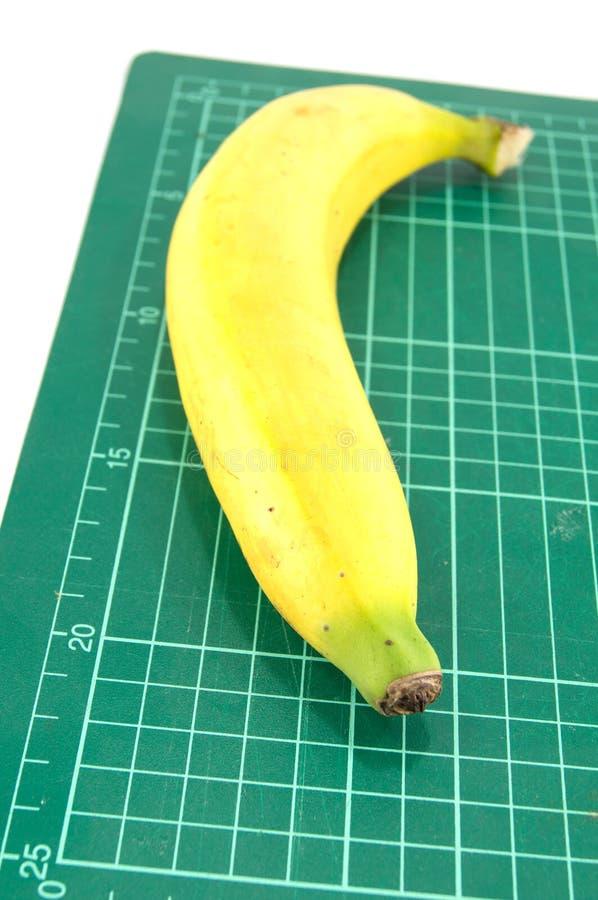 Banane auf Schneidematte stockbilder