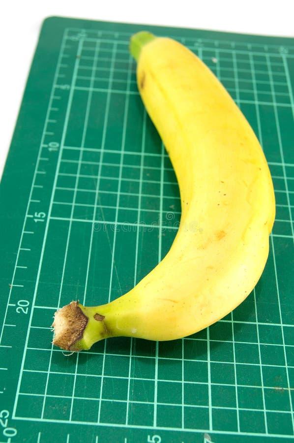 Banane auf Schneidematte lizenzfreie stockfotos
