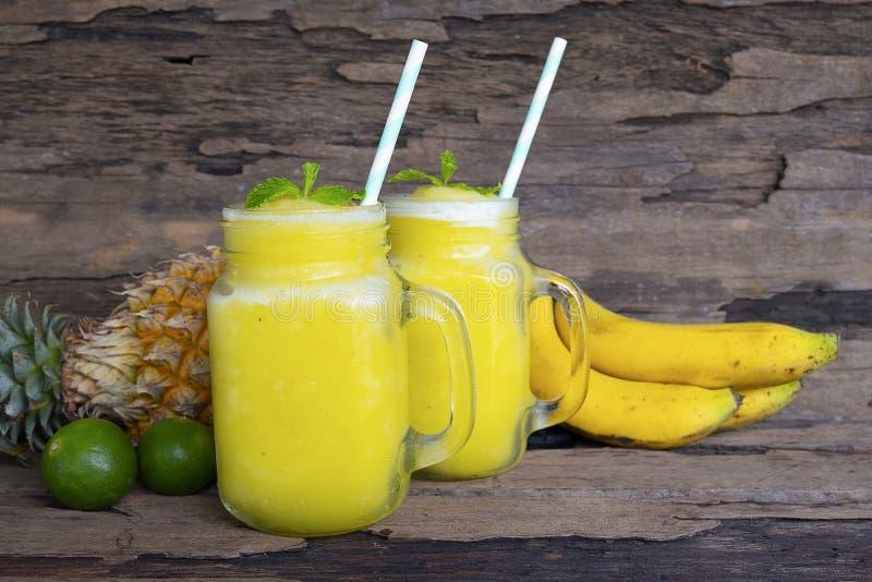 Banane avec la boisson saine jaune de jus d'ananas et de fruit de smoothies de pommes photo libre de droits