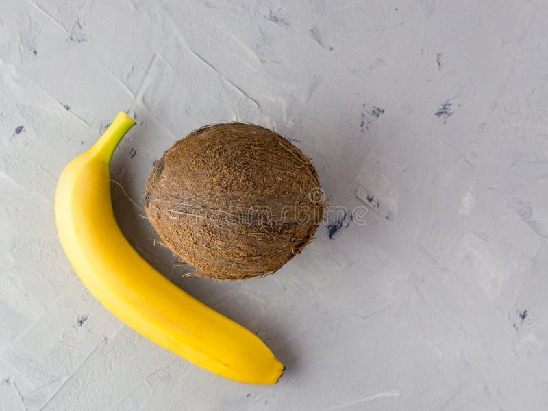 Banane et noix de coco sur le fond gris Vue sup?rieure Concept sain de nourriture de vegan photos stock