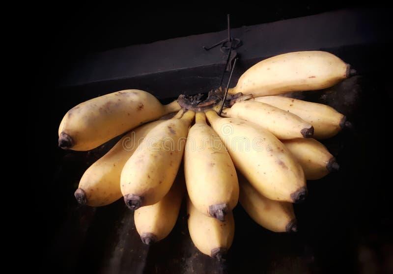 Banane gialle mature che appendono dentro un negozio immagini stock libere da diritti
