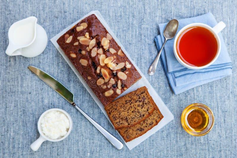 Banane, Karotte, Apfelkuchen, Laib mit Schokolade und Tasse Tee auf grauem Textilhintergrund Beschneidungspfad eingeschlossen stockbilder