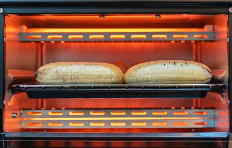 Banane mûre épluchée dans le grille-pain électrique chaud, faisant cuire le pain grillé de banane photographie stock