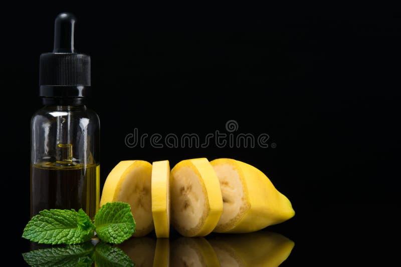 Banane mit grünen tadellosen Blättern und einer Flasche Duft für eine elektronische Zigarette auf einem schwarzen Hintergrund stockbild