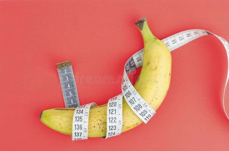 Banane mit messendem Band stockbilder