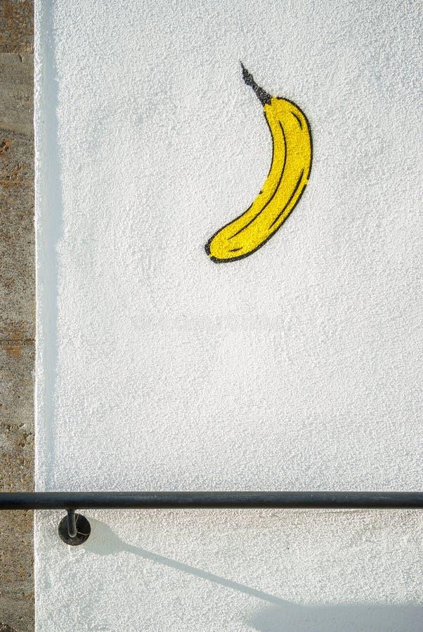 Banane peinte sur le graffiti blanc de mur de maison avec la balustrade image libre de droits